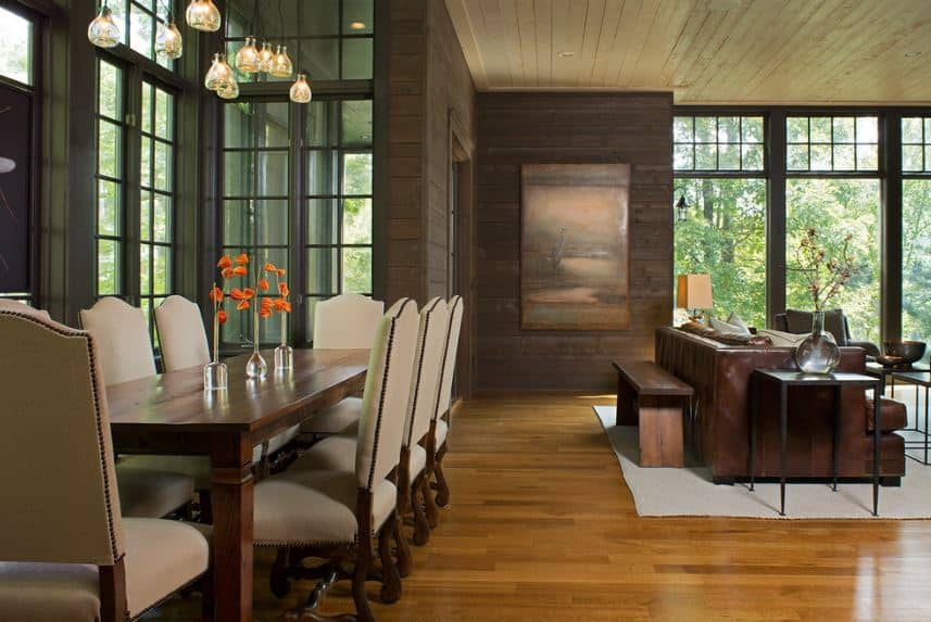 This dining area is a part of the large great room that has a different shade of brown each for the wooden shiplap ceiling, wooden walls and hardwood flooring. This provides a nice background for the elegant dining set that has light gray cushions for the chairs.