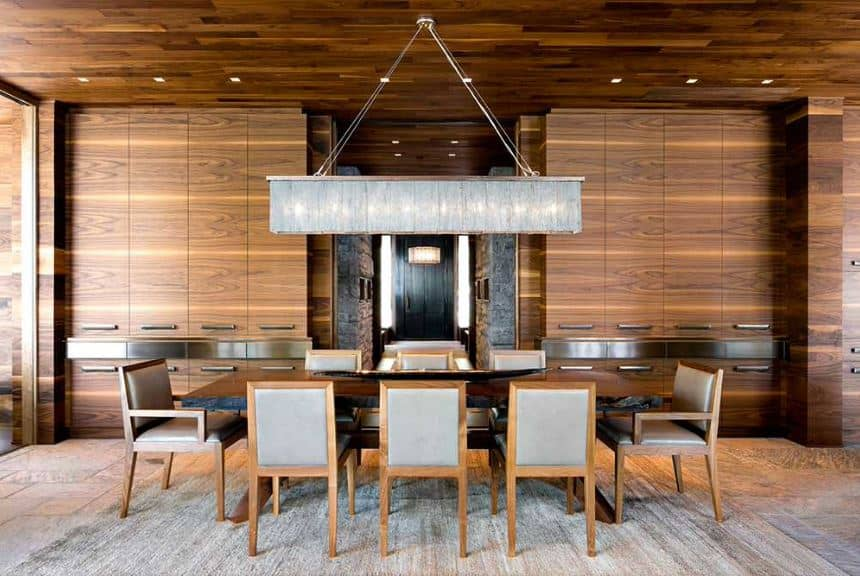 This is a grand dining room with an emphasis on the craftsmanship of the modern cabinets dominating the wooden walls that blend with the wooden ceiling and the large rectangular dining table that is topped with an elongated pendant light.