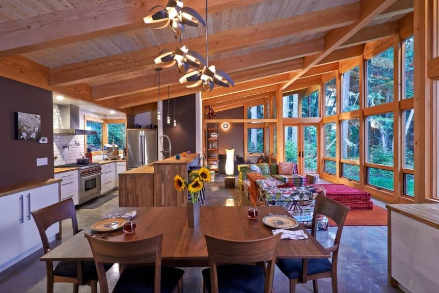 This informal dining area shares its wooden shed ceiling with exposed wooden beams with the rest of the great room that also houses the kitchen and the living room. This is paired well with the dark wooden hue of the wooden dining set that goes well with the chocolate brown walls.