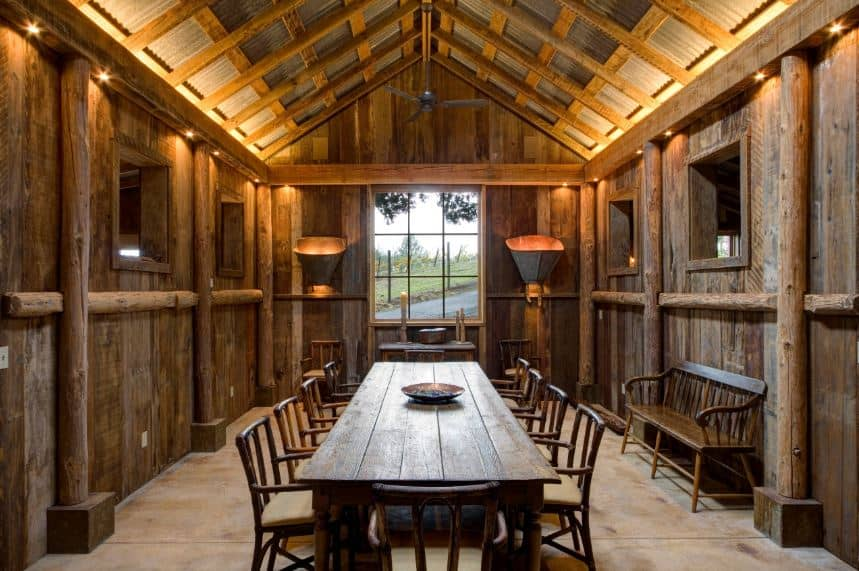 This homey and rustic log cabin dining room is dominated by the dark wooden hues of the wooden cathedral ceiling and walls that have exposed log beams that matches the rustic long rectangular dining table paired with wooden chairs.