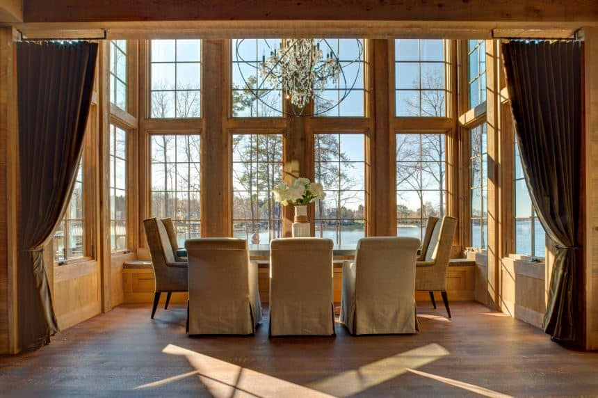 The real highlight of this dining room is the amazing lakeside scenery outside that is showcased by the tall windows that have bare wooden frames complementing the hardwood flooring and the large crystal chandelier hanging over the dining set.