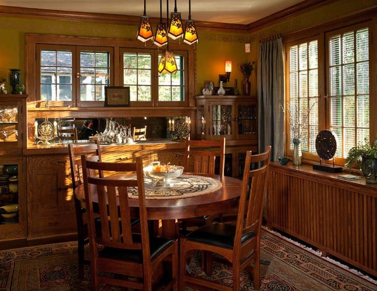 The wooden round table that seats four people on its wooden chairs with black leather seats is in a charming corner of the house that is dominated by the wooden structures with cabinets and storage against the dark green walls.
