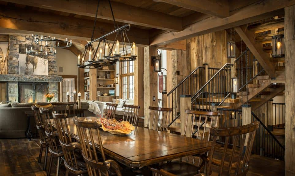 The wooden chairs of the rectangular wooden table has a charming slat back design that matches with the wrought iron railings of the wooden stairs with large wooden beams matching those of the wooden ceiling with exposed wooden beams.