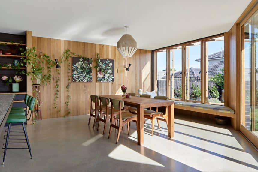 This bright cozy dining area has an abundance of natural light that is due to the glass windows with a cushioned bench beneath and the tall glass doors all with the same wooden frame matching the wall at the head of the wooden table adorned with artworks and plants.