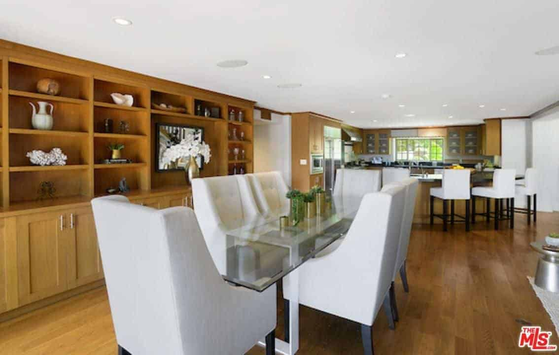 This dining area has a yin and yang balance between the bright white elements and the brown wooden elements. a wide white ceiling pairs well with the white cushioned seats of the modern glass-top table. This is contrasted by the hardwood flooring and the large wooden structure dominating the wall with its shelves and cabinets.