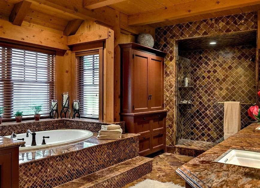 Brown primary bathroom with stylish tiles walls and floors. The walk-in shower looks amazing with its design as well as the tub platform.