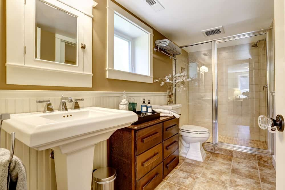 Primary bathroom with brown walls and brown tiles floors. The room offers a pedestal sink and a walk-in shower.
