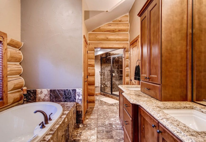 Primary bathroom featuring stylish tiles flooring and a tall ceiling. It offers two sinks, brown cabinetry, a drop-in tub and a walk-in corner shower.