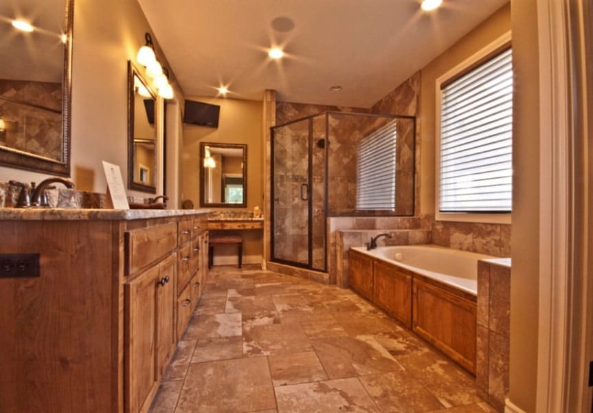 Primary bathroom featuring brown walls and brown tiles flooring. There's a sink counter with two sinks along with a drop-in tub, a powder desk and a walk-in corner shower. The room is lighted by wall and recessed ceiling lights.