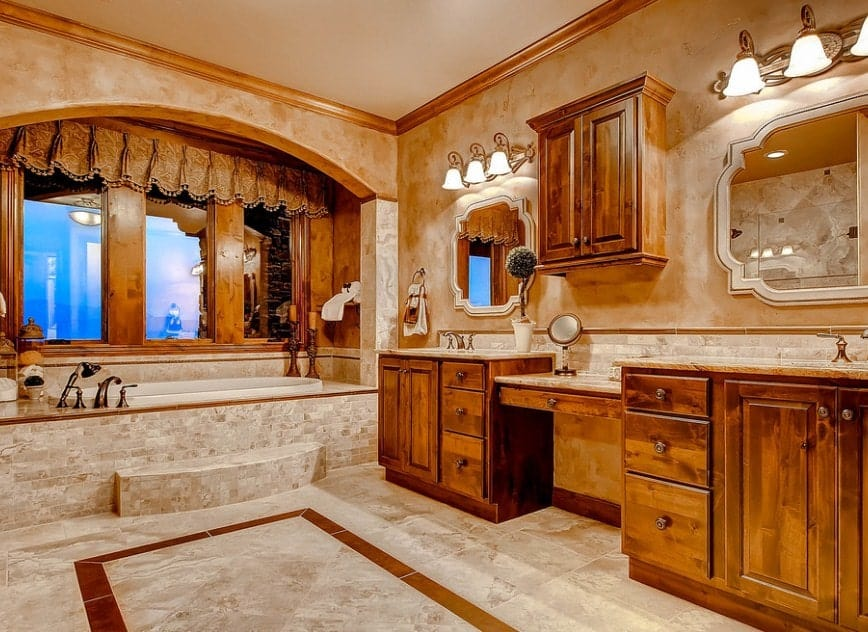 Classy primary bathroom featuring decorated walls and floors. It offers two sink counters and a powder desk lighted by gorgeous wall lights. The room also has a drop-in tub.