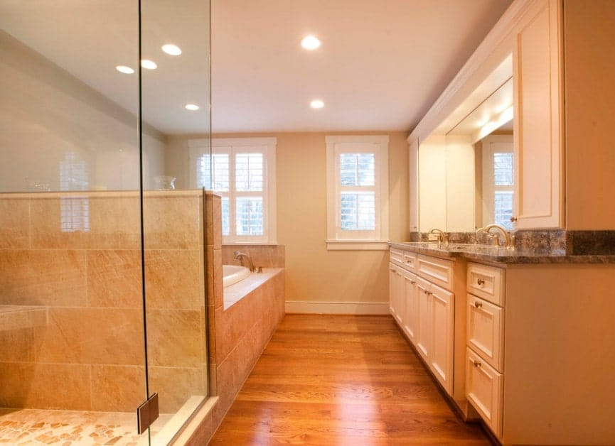 Brown primary bathroom featuring a brown sink counter with two sinks along with a drop-in tub and a walk-in shower. The room features hardwood flooring and recessed lights.