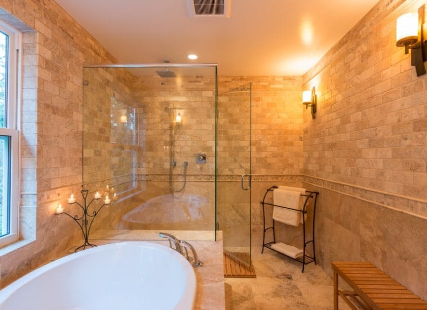 Primary bathroom featuring a walk-in shower and a drop-in tub. The room is lighted by wall lights.