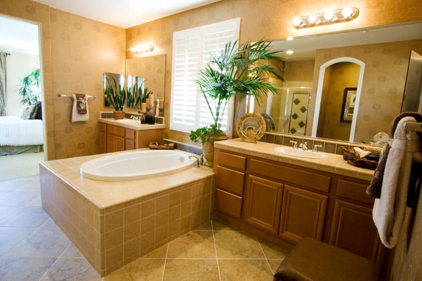 A primary bathroom with decorated brown walls. It offers a drop-in tub on a tiles platform. The two sink counters are lighted by classy wall lights.