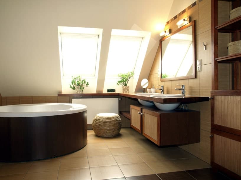 This primary bathroom boasts a stylish sink counter with vessel sinks along with a round drop-in tub.