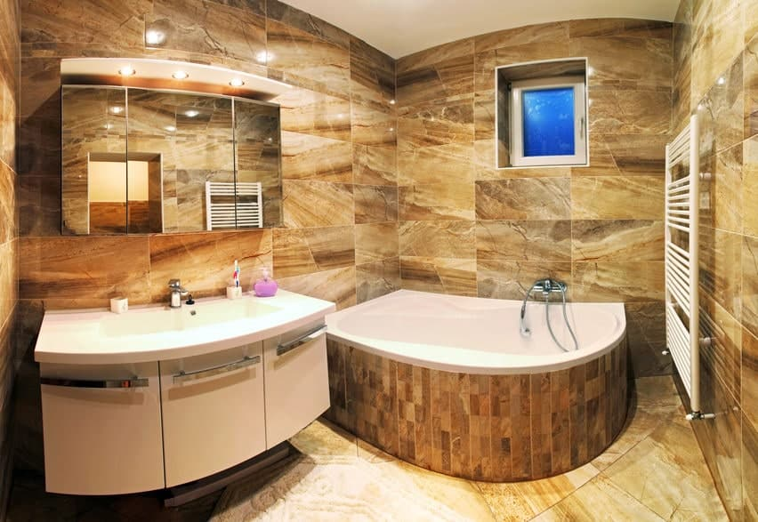 Small primary bathroom featuring brown tiles floors and walls. The room offers a floating vanity sink and a drop-in corner tub.