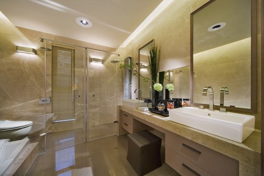 Primary bathroom featuring beautiful walls and flooring. The room offers a large walk-in shower and a sink counter with large vessel sinks.