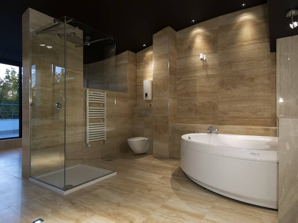 A modern primary bathroom with beautiful tiles flooring and walls. The room offers a walk-in shower booth and a large drop-in tub.