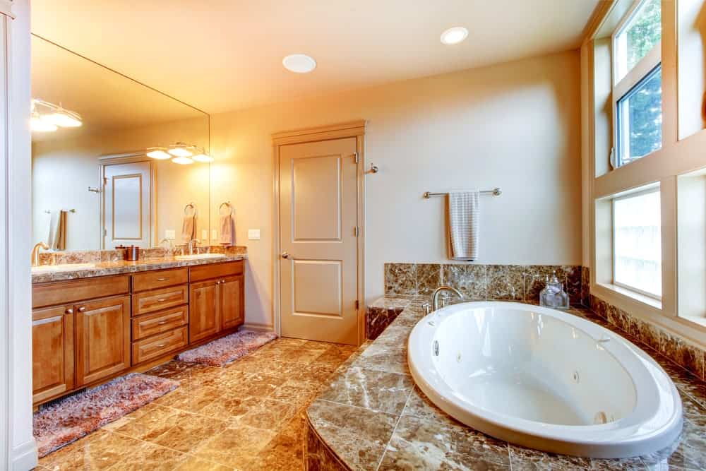 Bright primary bathroom featuring stylish brown tiles flooring. It has a sink counter matching the tiles flooring.