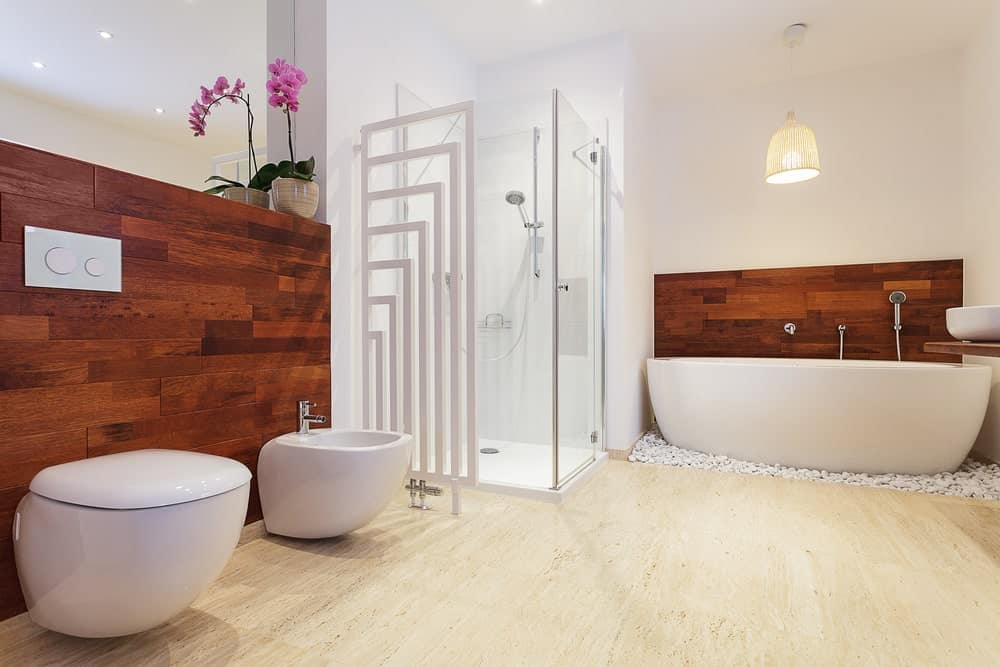 Spacious bright primary bathroom featuring wooden walls and hardwood flooring. It has a large freestanding deep soaking tub and a walk-in shower space.