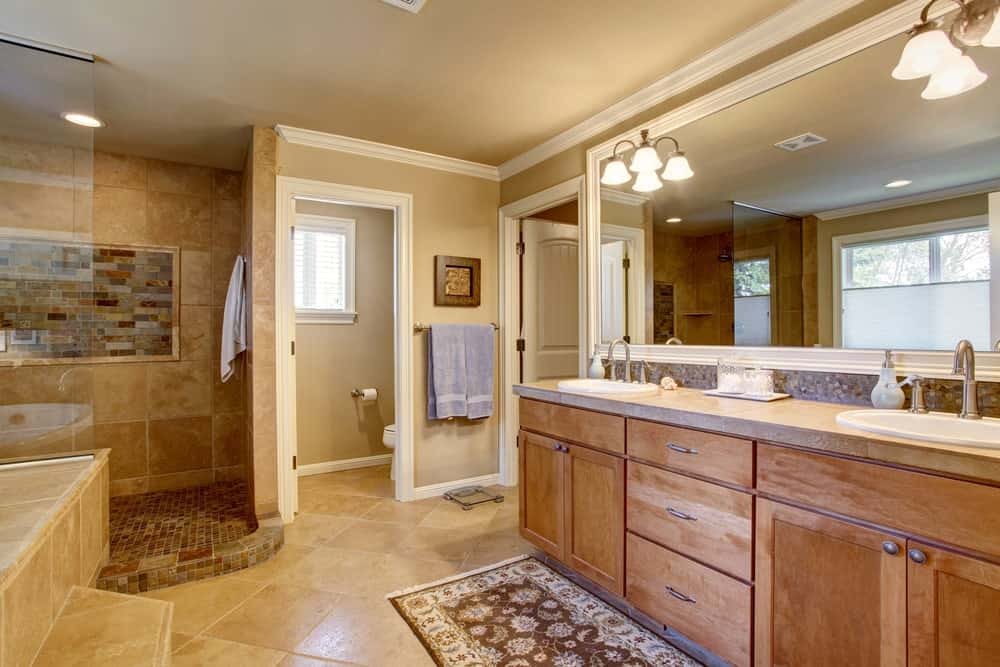 A spacious primary bathroom featuring brown tiles floors and walls. It features a sink counter with two sinks lighted by gorgeous wall lights. The room also has a walk-in corner shower area and a drop-in tub.