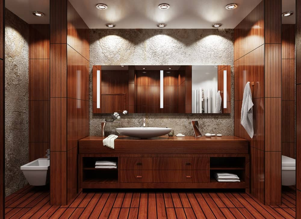 Brown primary bathroom with hardwood floors and a beautiful brown sink counter with a large vessel sink.