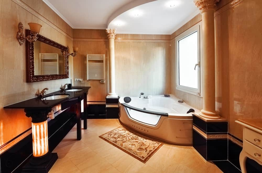 Classy, Romantic-style primary bathroom with a black sink counter, a drop-in corner tub and elegant wall lights.