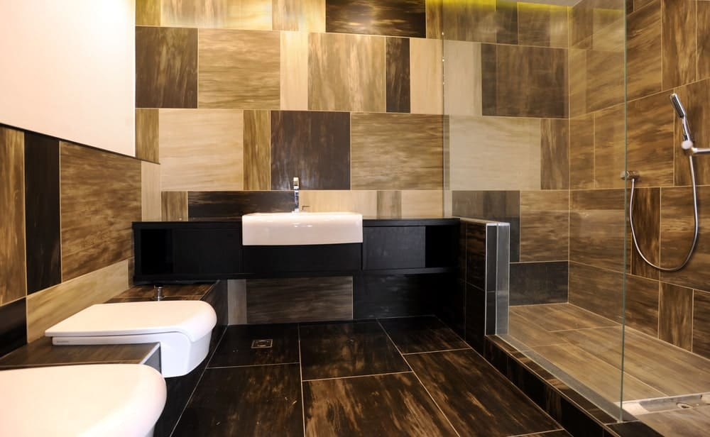 Primary bathroom boasting stylish tiles walls and floors. It features a black floating vanity sink along with a walk-in shower.