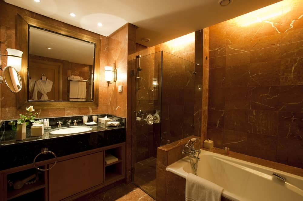 Small primary bathroom featuring a black sink counter, a drop-in tub and a walk-in shower surrounded by brown walls.