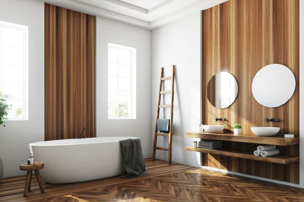 Primary bathroom featuring a white and brown color scheme. The herringbone-style flooring looks absolutely stylish. The room offers a floating vanity with a pair of vessel sinks along with a large freestanding soaking tub.