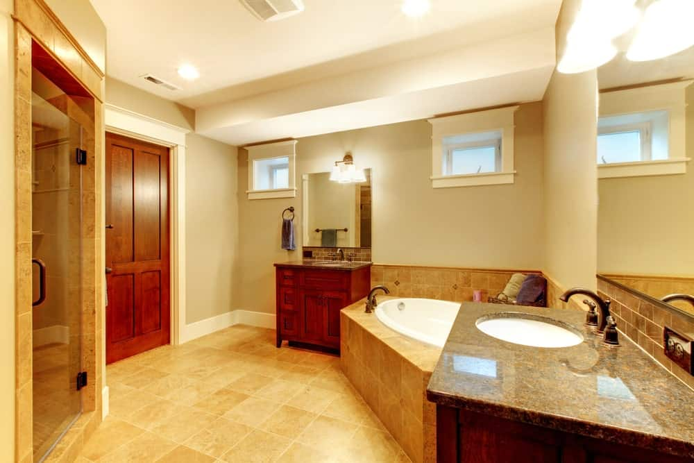 Spacious primary bathroom featuring brown tiles flooring. The room offers a walk-in shower room, a pair of sink counters and a drop-in corner tub.