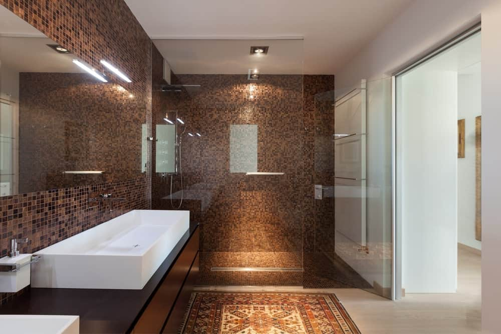 Modern primary bathroom featuring tiny brown tiles walls. It offers a large vessel sink and a walk-in shower area.