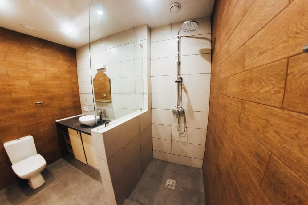 A small primary bathroom with brown walls. It features a small sink counter with a vessel sink along with a walk-in shower area.