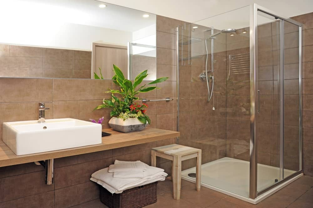 This primary bathroom features brown tiles walls and floors. The room also offers a vessel sink and a walk-in shower area.