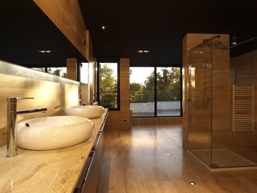 Spacious primary bathroom boasting brown floors and walls, along with a black ceiling. The room offers a marble sink counter with two vessel sinks along with a walk-in shower area.