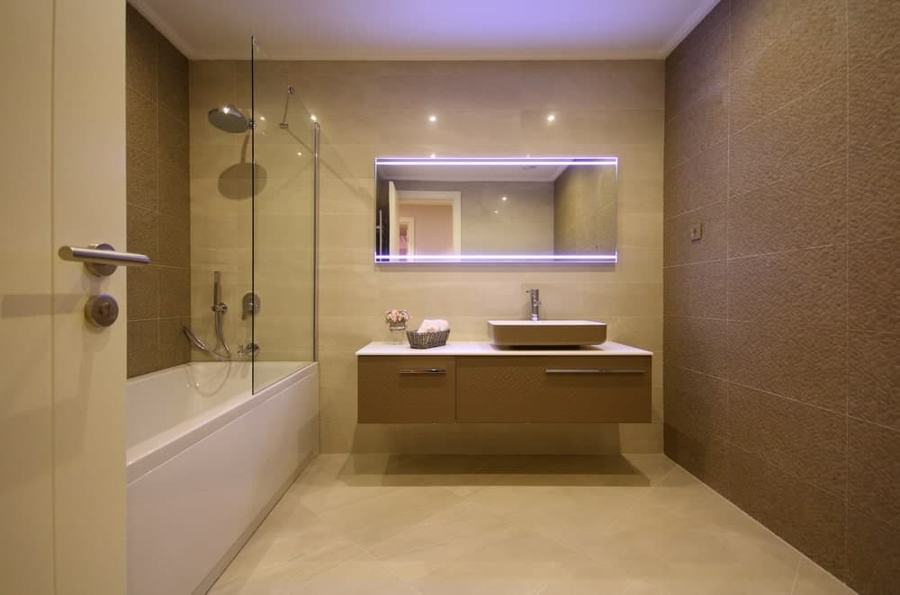 A simplistic modern primary bathroom featuring a brown tiles wall, a floating vanity with a vessel sink and a bathtub and shower combo.