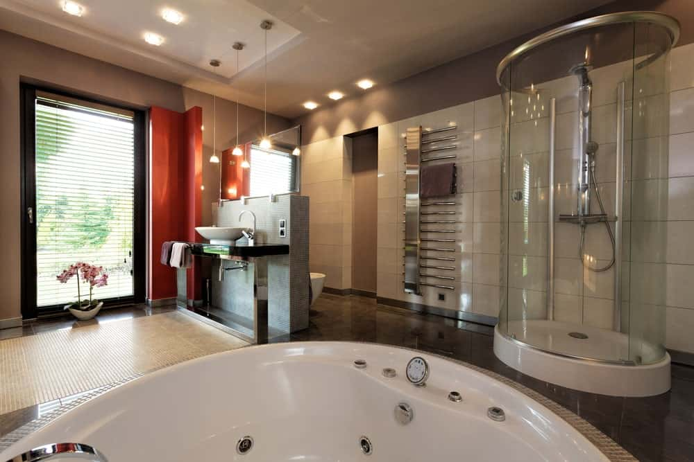 Modern primary bathroom featuring a walk-in shower booth, a deep soaking tub and a modern sink counter with a vessel sink.