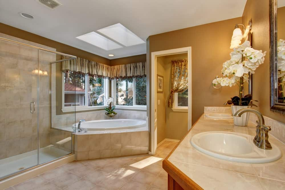 A classy primary bathroom featuring brown walls and tiles flooring. The room offers a drop-in corner tub and a walk-in shower. The room has skylights as well.