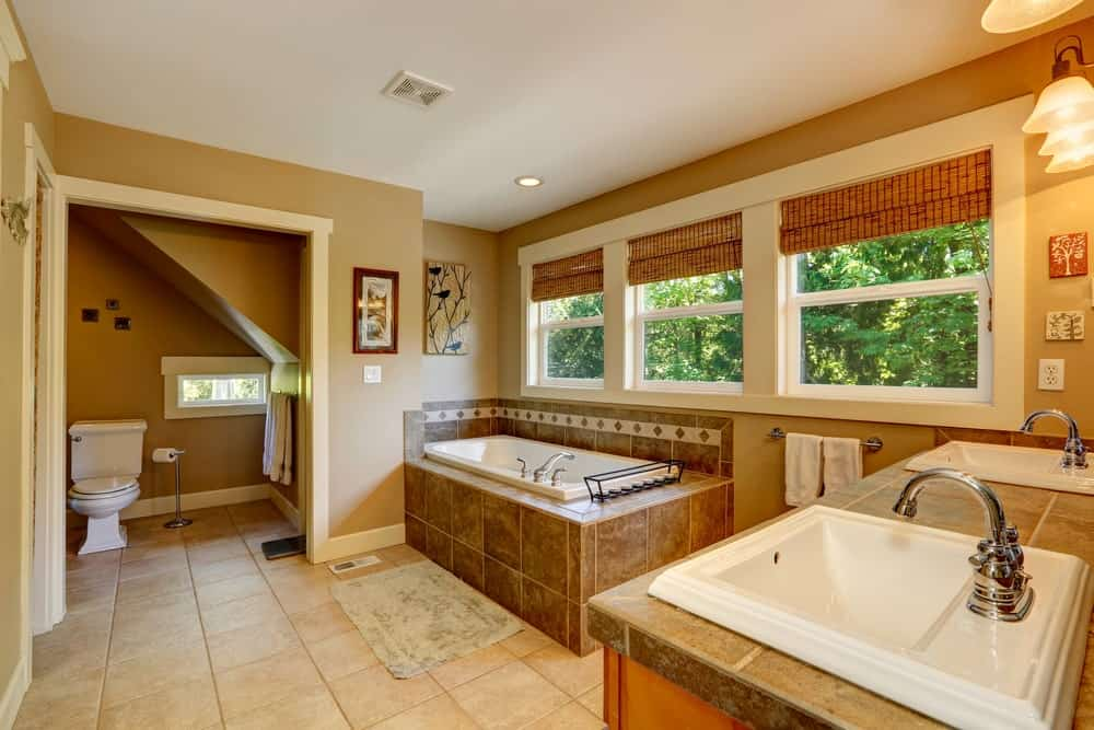 Primary bathroom with brown walls and tiles flooring. The room has a drop-in tub with a brown tiles platform along with a sink counter with two sinks.