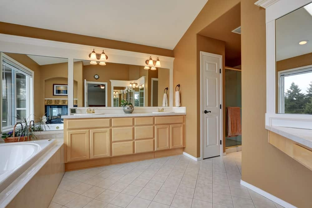 A spacious primary bathroom featuring brown walls and white tiles floors. There's a sink counter with two sinks and is lighted by classy wall lights. The room also offers a drop-in tub.