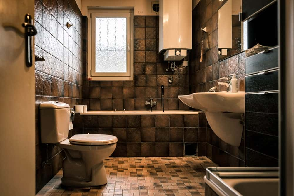 This primary bathroom features stylish brown tiles walls and floors. The room also has a drop-in tub, a toilet and a large sink.