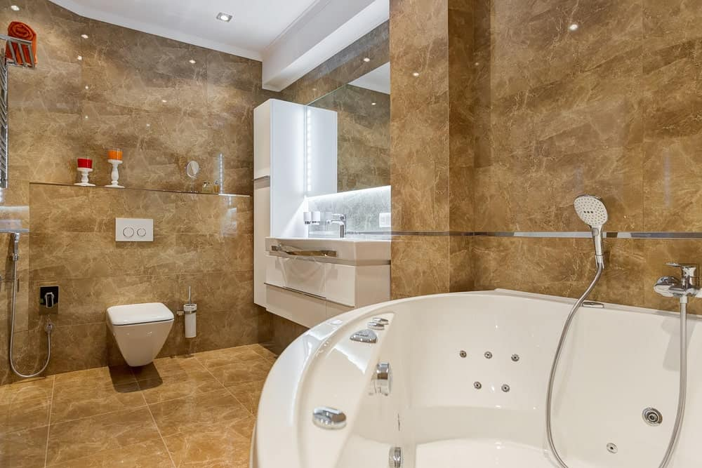 Modern primary bathroom featuring brown tiles flooring and walls. The room has a floating vanity sink along with a deep soaking tub.