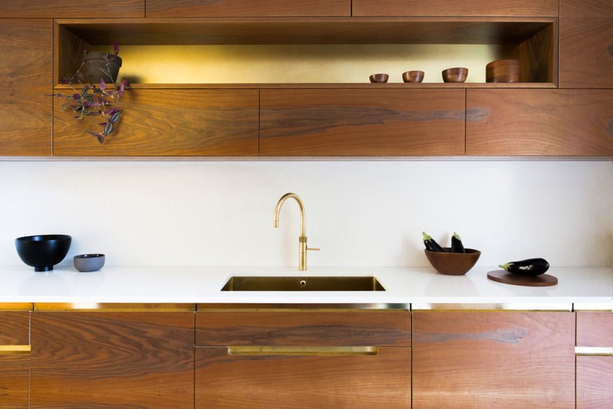 Bespoke walnut kitchen cupboards with unlacquered brass kitchen sink.