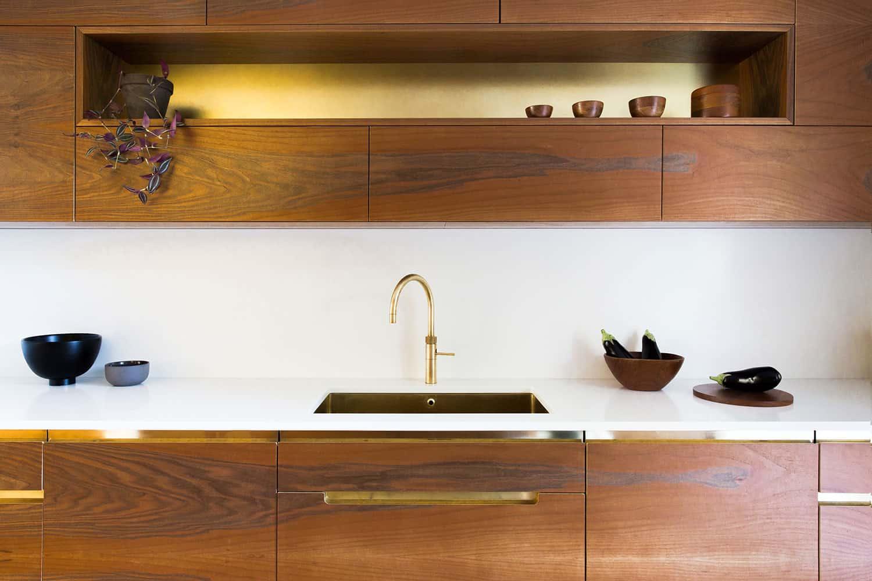 Bespoke walnut kitchen cupboards with unlacquered brass kitchen sink.