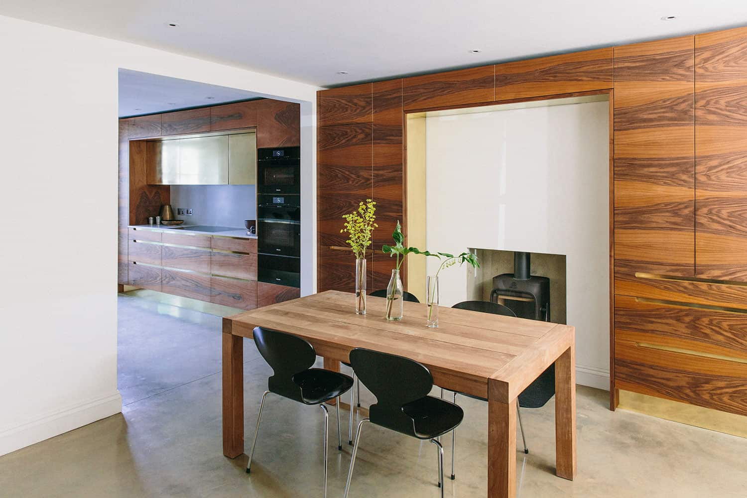 Bespoke beautiful kitchen interior as seen from the dining room with a fireplace.