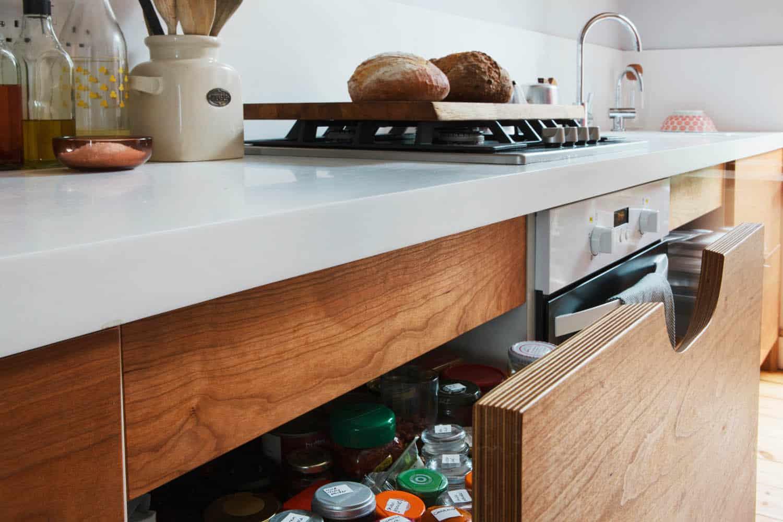 Kitchen drawer made of veneered plywood with scoop handle under the kitchen worktop.