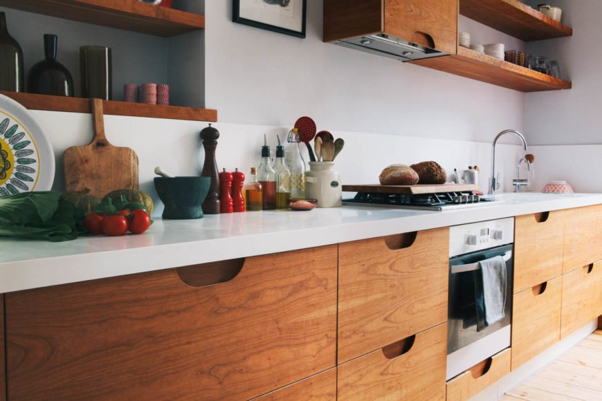 Single wall kitchen featuring veneered plywood pull-out drawers under the countertop.