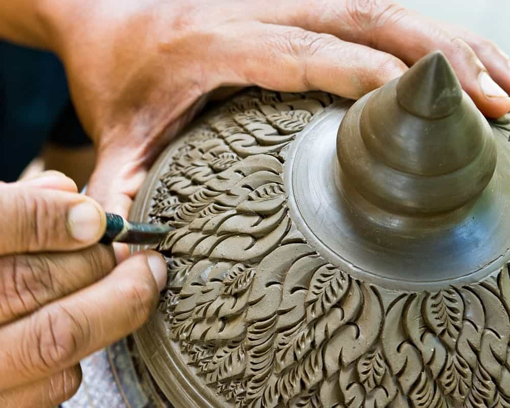 Carving a clay earthenware.