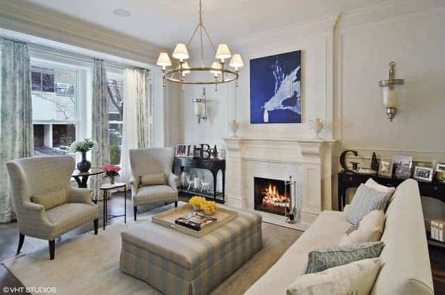 This light hued living room has a dash of color in the form of a blue painting mounted above the white mantle of the fireplace that brings warmth to the light hued couch and cushioned armchairs above a light gray area rug.