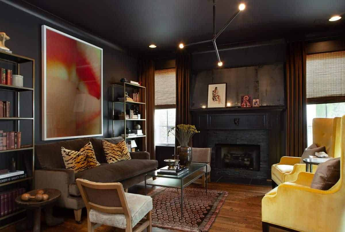 This is a stunning black living room with black walls and ceiling adorned with a large colorful artwork that matches the tiger print pillows of the brown velvet sofa contrasted by a couple of yellow cushioned armchairs.