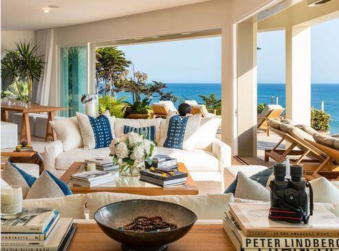 The bright demeanor of this living room is due to the large open sides that offer a great view of the ocean that is augmented by the blue details of the pillows on the white comfortable couches that is paired with a glass-top wooden coffee table.